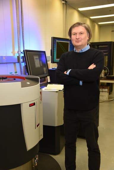 Krzysztof Gofryk standing next to a desk with his arms folded.