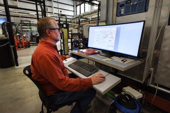 A man sitting at a computer control terminal.